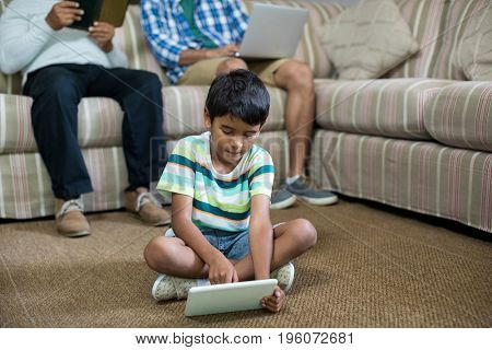Boy using tablet with father and grandfather sitting on sofa in background