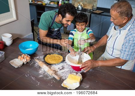 High angle view of father and grandfather looking at boy making food while standing in kitchen at home