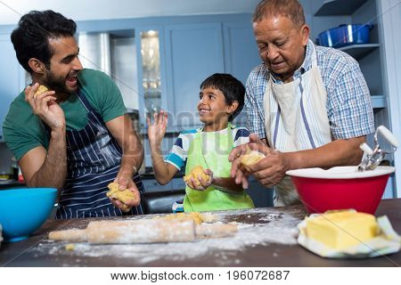 Playful family holding dough while preparing food in kitchen at home