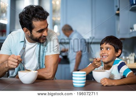 Father and son having breakfast at table with man in background