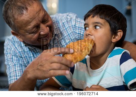 Grandfather feeding croissant to grandson while having breakfast