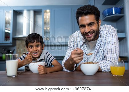 Portrait of father and son having breakfast at home