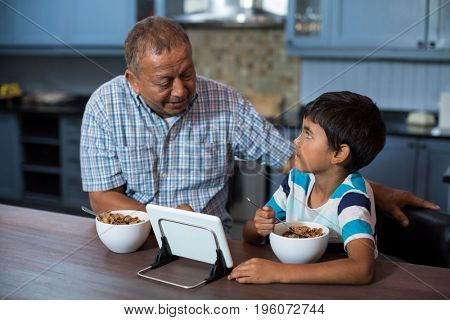 Grandfather and grandson using tablet computer while having breakfast at home