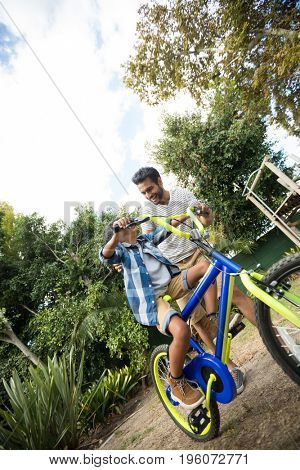 Tilt image of father assisting son for riding bicycle in yard against sky