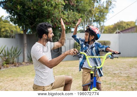 Father and son doing high five while cycling in yard