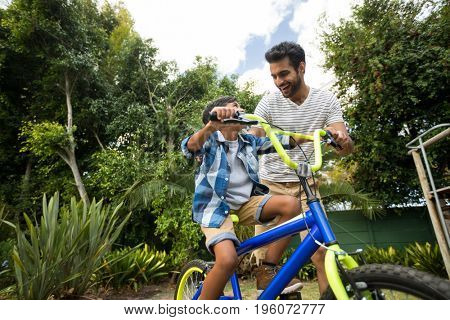 Happy father assisting son for riding bicycle in yard