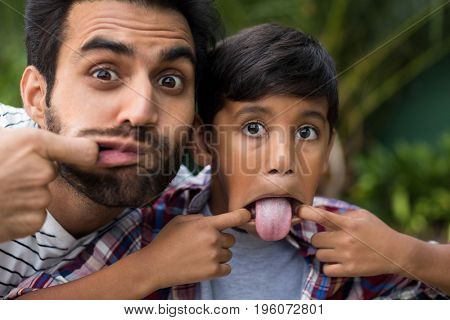 Portrait of father and son teasing while playing in yard