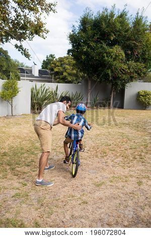 Rear view of father assisting son while riding bicycle on field in yard