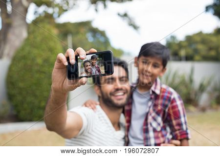 Happy father and son talking selfie in yard