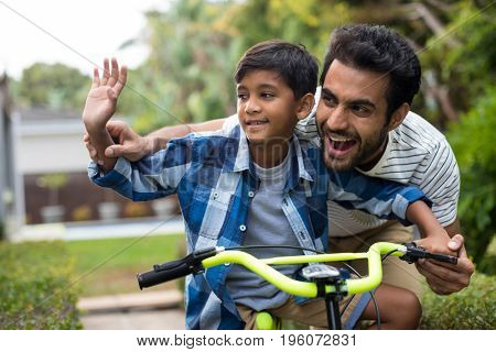 Father and son waving hand while cycling in yard