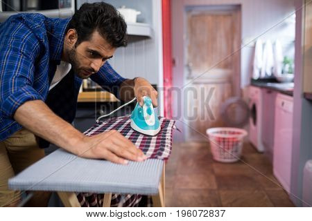 Young man ironing shirt on board at home