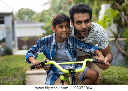 Father looking away while assisting son for cycling in yard