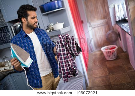 Man with iron looking at shirt while standing by board