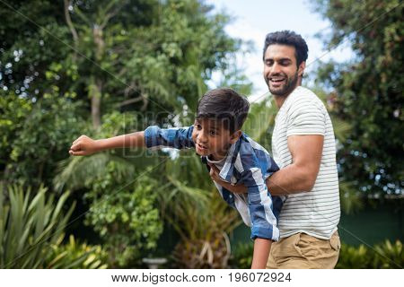 Playful father carrying son while playing at yard