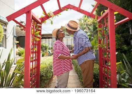 Side view of senior couple talking while standing in yard