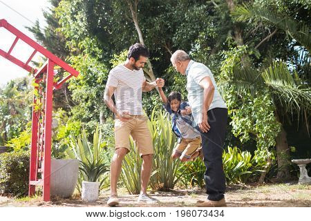 Father and grandfather with boy at park during sunny day
