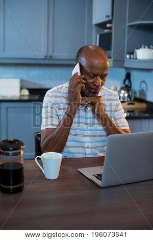 Senior man using laptop at table in kitchen