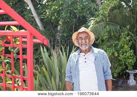 Portrait of senior man standing by metallic structure in yard