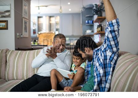 Happy grandfather and father with boy sitting on sofa in living room at home