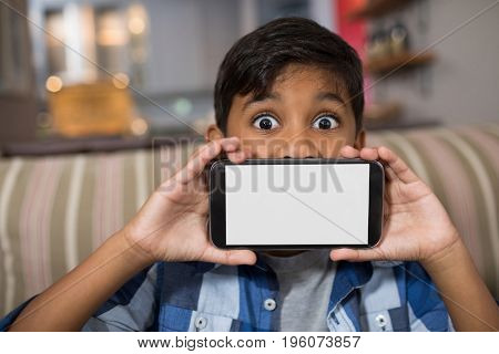Portrait of boy showing smartphone while sitting on sofa at home