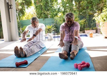 Senior couple doing stretching exercise while sitting on exercise mat in yard