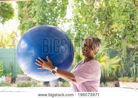 Portrait of woman holding fitness ball while standing in yard