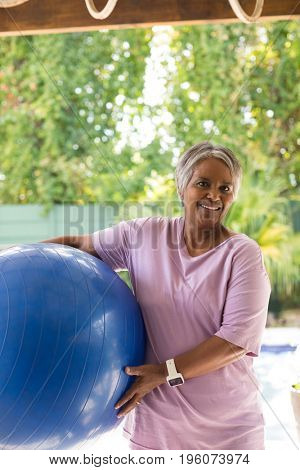 Portrait of smiling woman holding fitness ball while standing under shed in yard