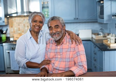 Portrait of couple with arm around in kitchen at home