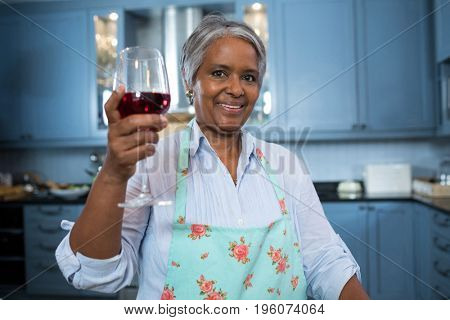 Portrait of woman showing wineglass while standing in kitchen at home