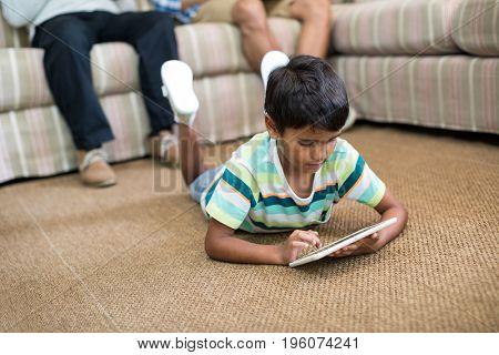 Boy using tablet lying on carpet with father and grandfather sitting on sofa in background
