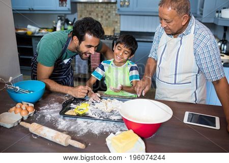 Boy preparing food while standing with father and grandfather in kitchen at home