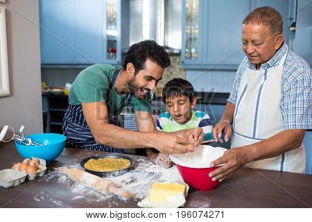 Boy looking at father breaking egg while preparing food with grandfather in kitchen at home