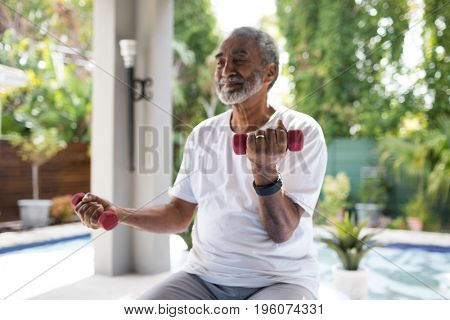 Senior man lifting dumbbell while exercising in yard