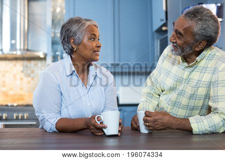 Couple talking while having coffee in kitchen at home