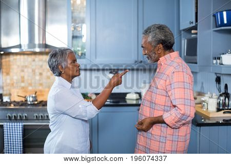 Side view of displeased couple standing in kitchen at home