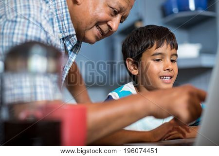 Close up grandfather assisting grandson using laptop in kitchen at home