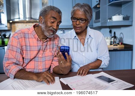 Couple using calculator while discussing over document in kitchen