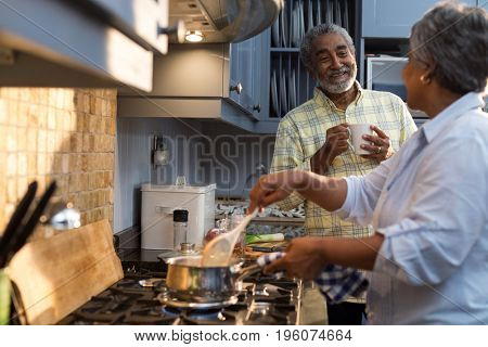 Smiling man coffee cup talking with woman preparing food while standing in kitchen