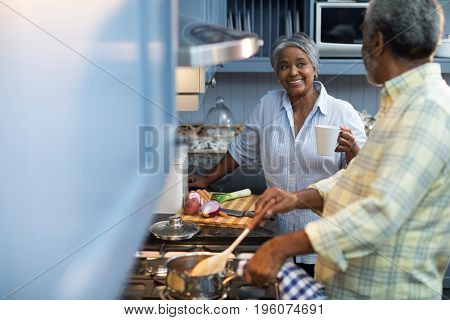 Smiling woman coffee cup talking with man preparing food while standing in kitchen