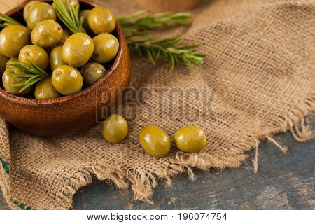 Green olives with rosemary in wooden container on jute