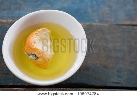 Piece of bread soaked in olive oil in white bowl