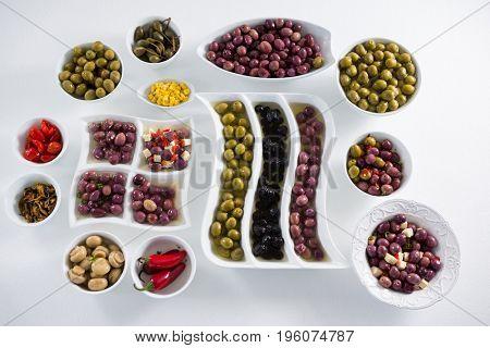Various pickled olives arranged on white background