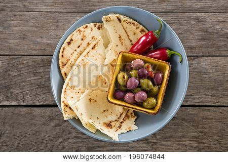 Close-up of marinated olives, food and chili pepper on wooden table
