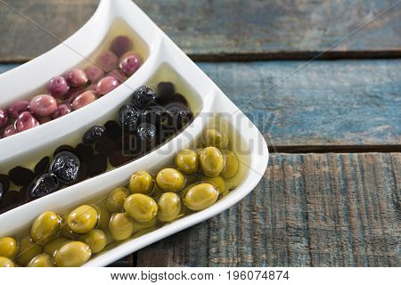 Various pickled olives in platter on wooden table
