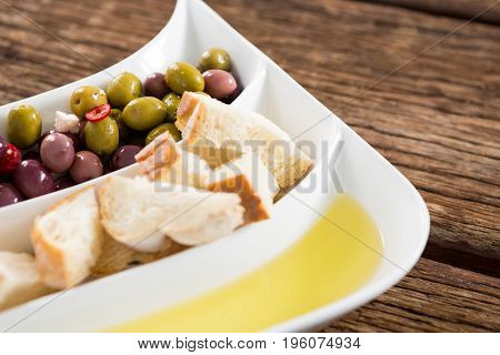 Close-up of marinated olives, bread pieces and olive oil in platter