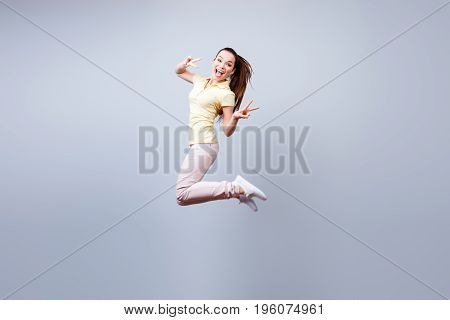 Funky Young Teen Is Jumping Up, Wearing Casual Clothes, Gesturing A Peace Signs. Happiness, Dream, F