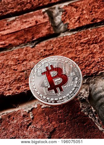 Digital currency physical silver bitcoin coin with red sign on brick wall.