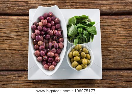 Marinated olives with herbs in bowl on wooden table