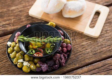 Pickled olives and vegetables with rosemary in bowl on wooden table