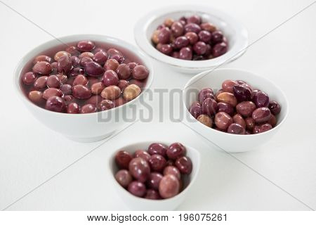 Close-up of pickled olives in bowls on white background